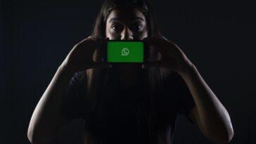 woman holding black smartphone at Whatsapp logo