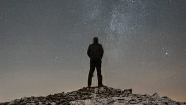 man standing on cliff duirng nighttime