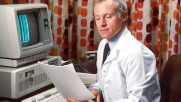 man reading papers in front of computer