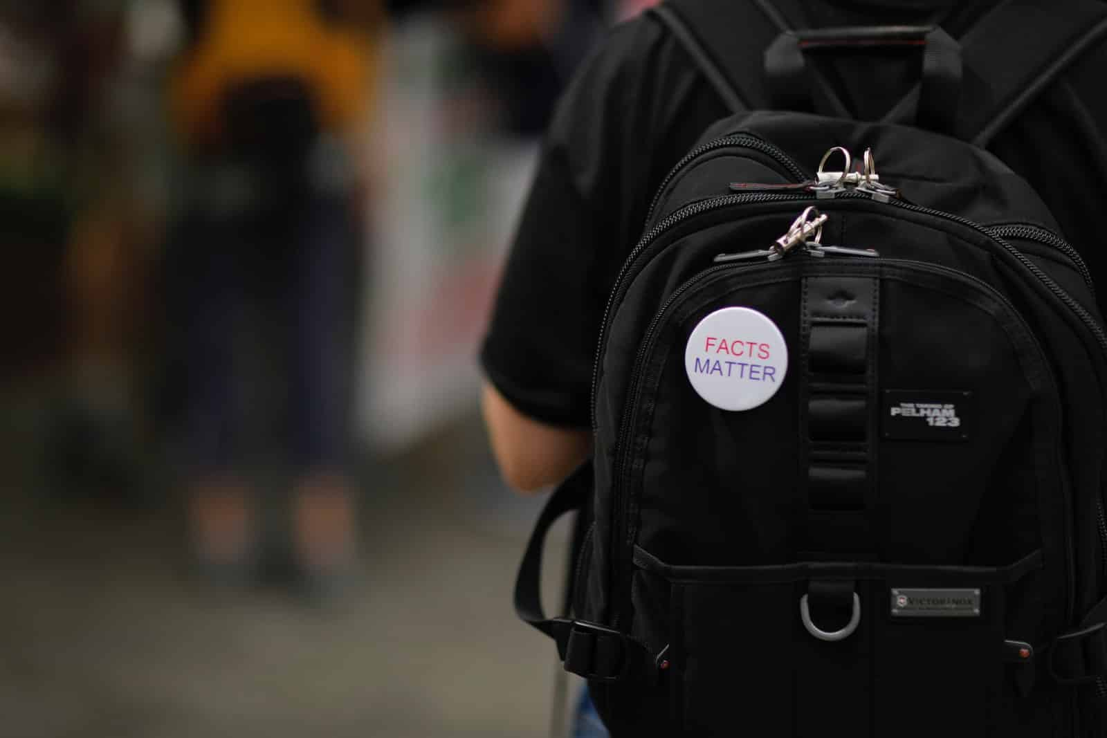 """A white""""Facts matter"""" pin on a black backpack on a person's back"""